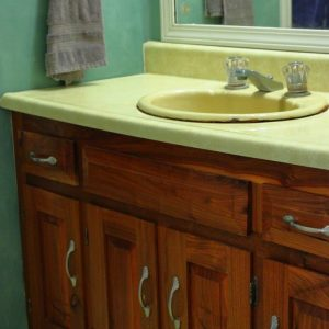 Photo of bathroom vanity with yellow countertop, green wall and wood bathroom cabinet