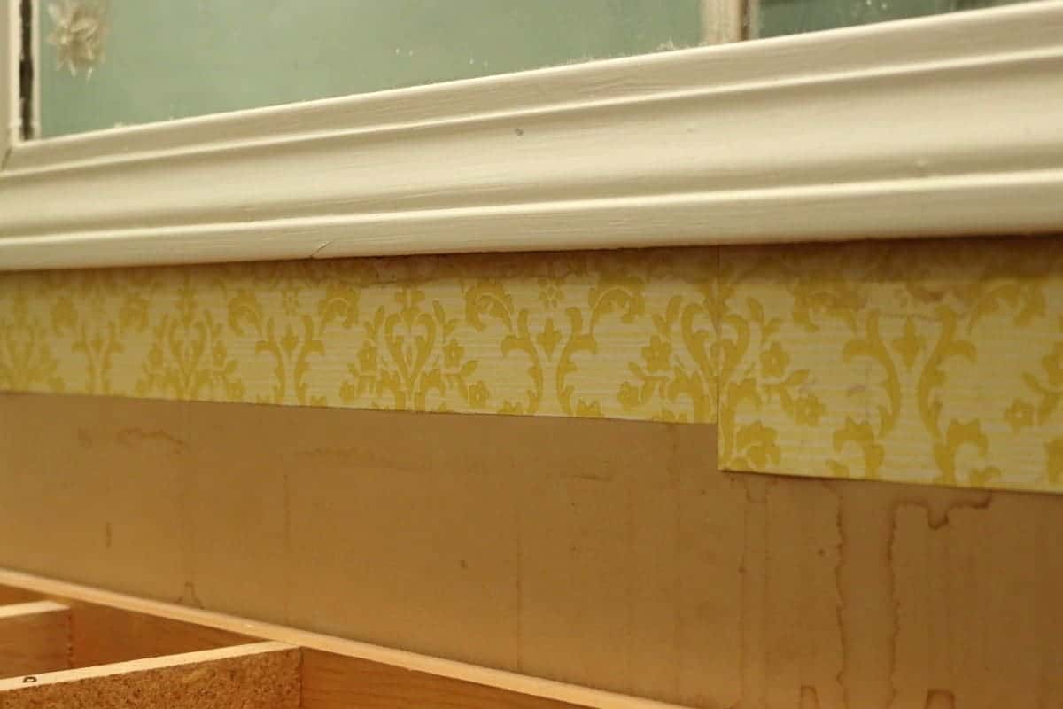 Photo of old yellow wallpaper and framed mirror before a DIY bathroom mirror frame project.
