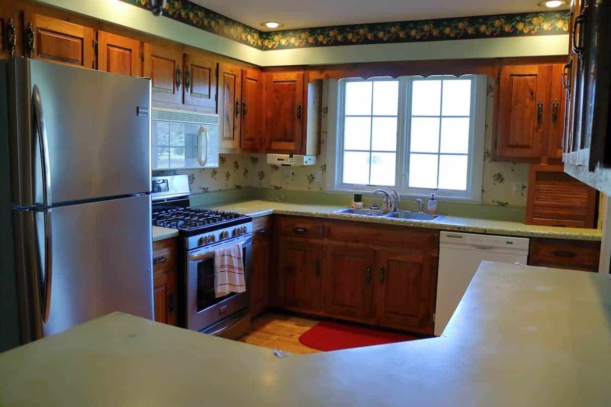 Kitchen renovation before - green counters, large window, and stainless steel appliances