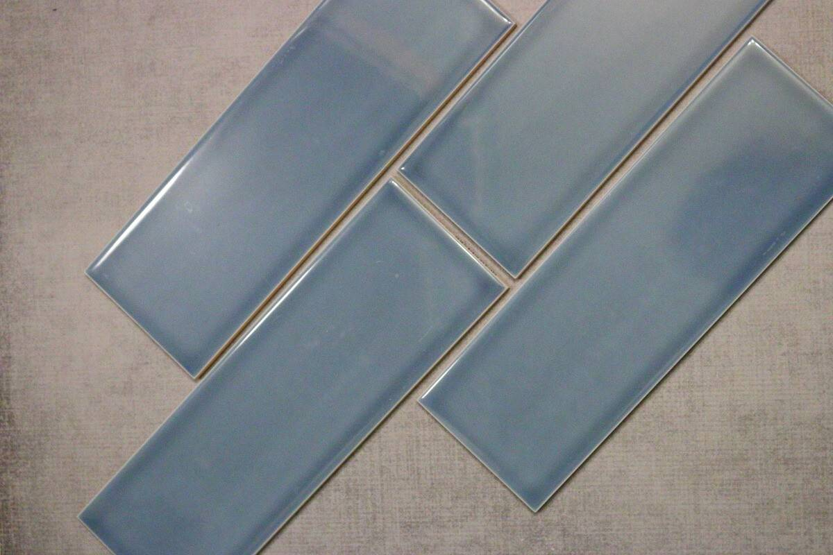 Blue subway tile on grey background for a bathroom remodel