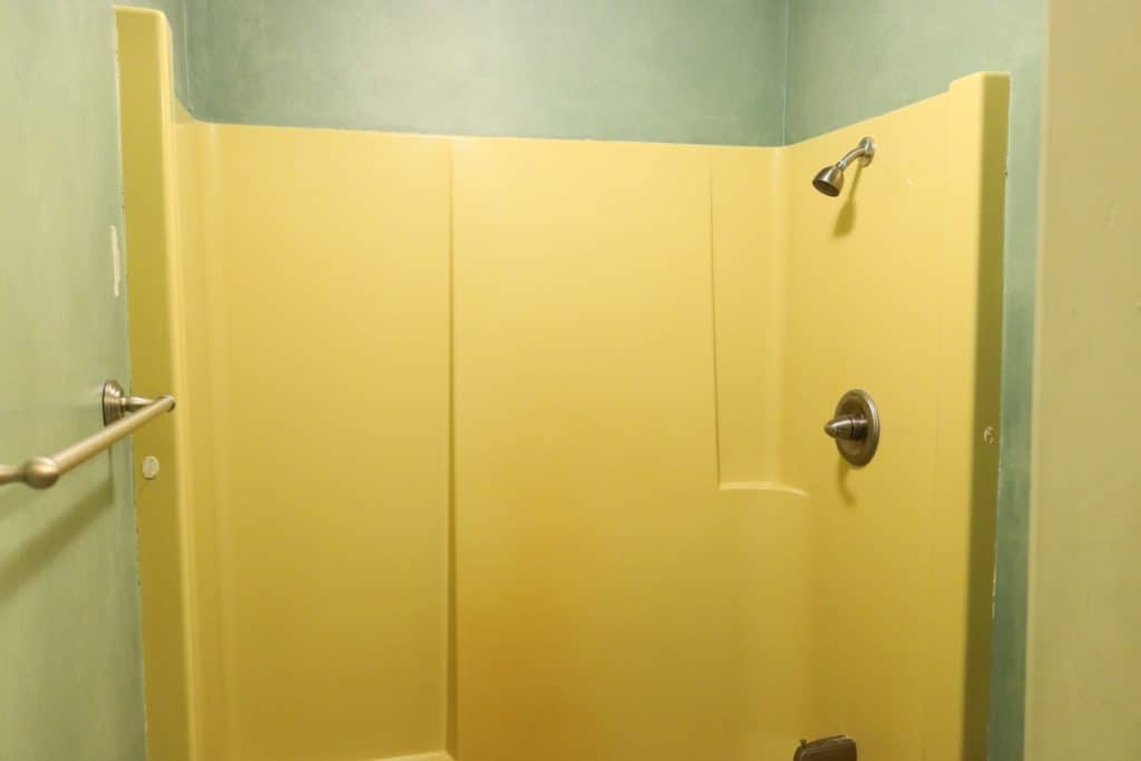 bathtub refinishing kit before picture of a yellow shower