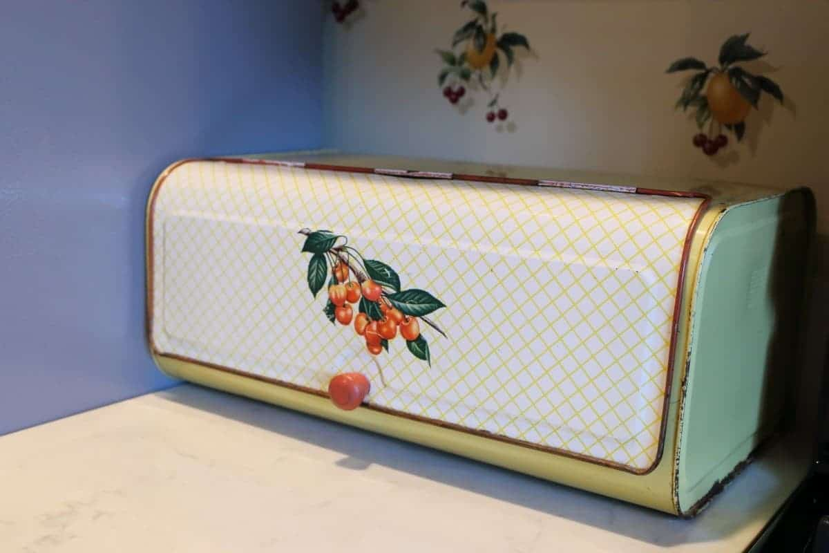 Vintage yellow bread box with cherries on the front.