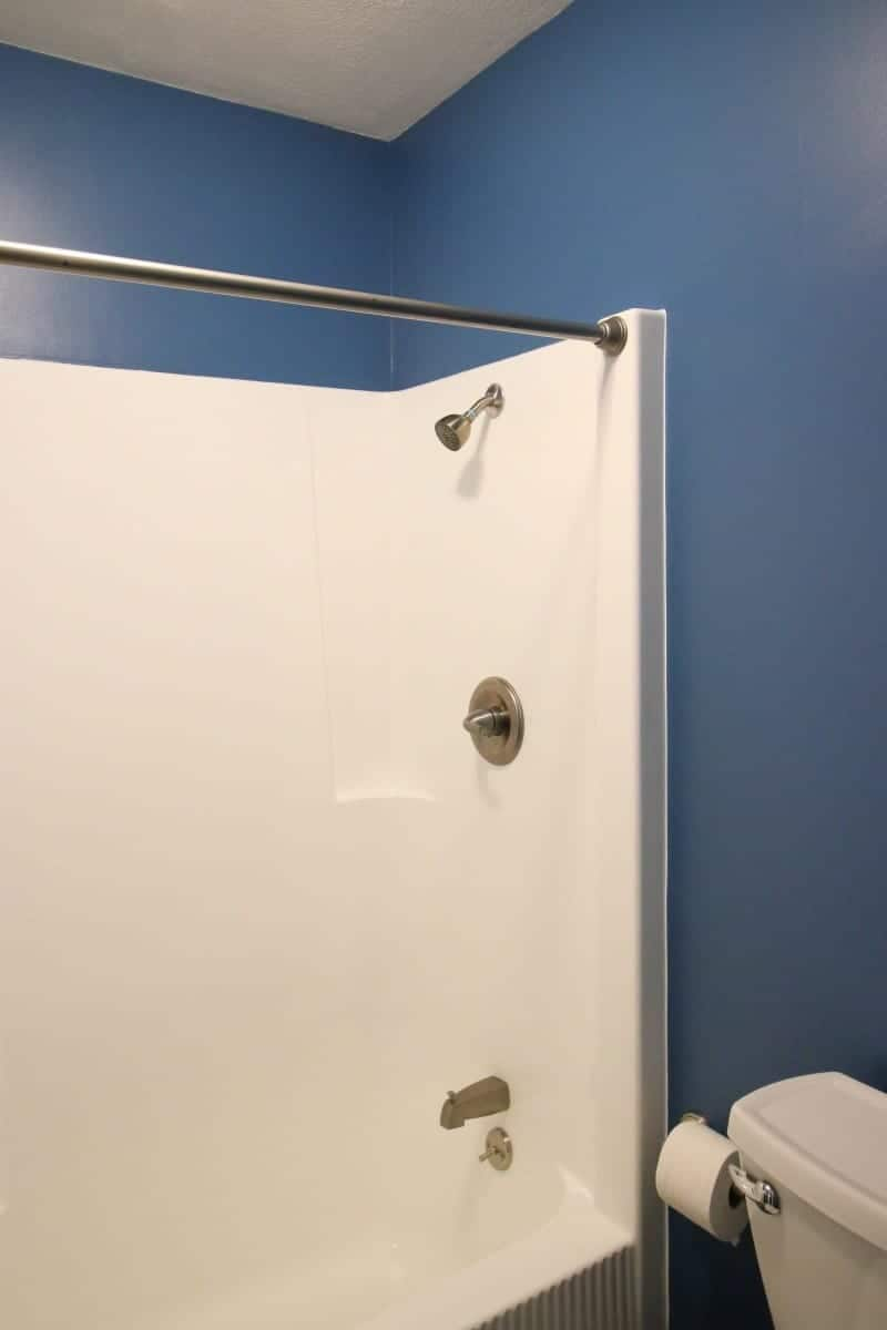 Photo of white refinished bathtub in a dark blue bathroom.