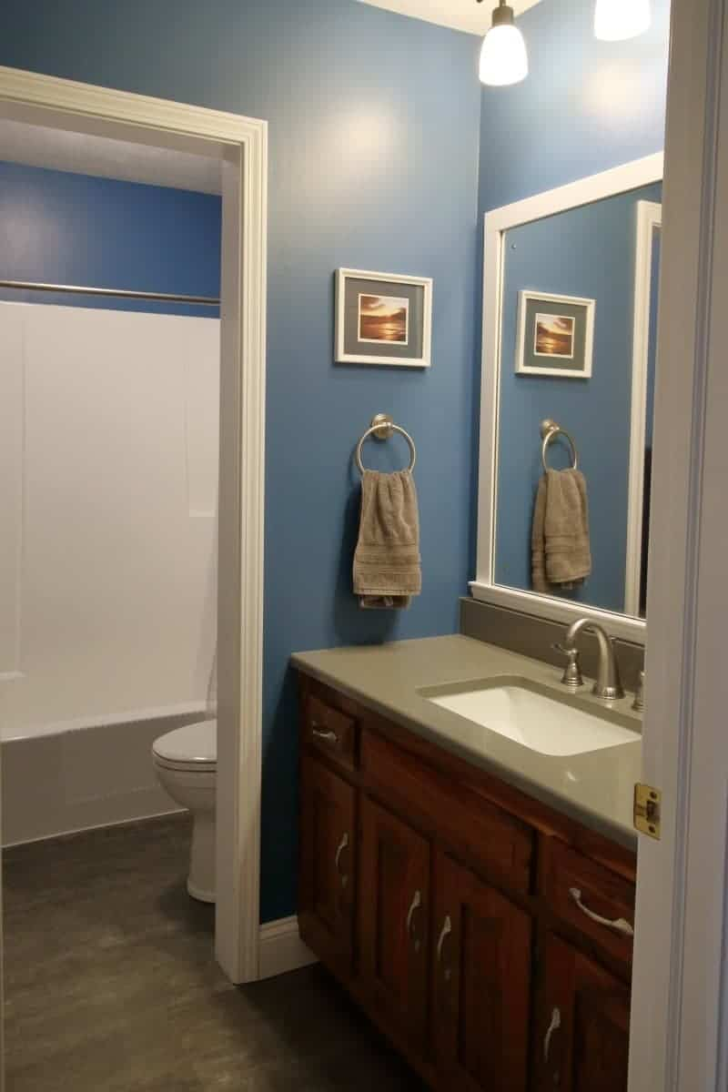 Photo of dark blue bathroom with white wood DIY bathroom mirror frame project