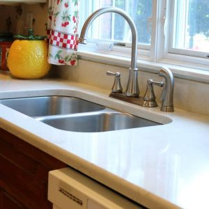 Kitchen remodel with white quartz countertop, undermount stainless steel sink and brushed nickel faucet.