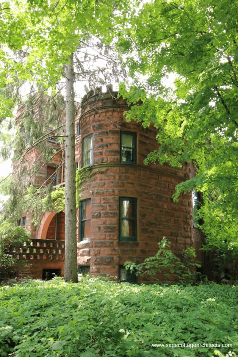 Side view of a typical Richardsonian Romanesque home - red ashlar walls with a round turret and lots of foliage.