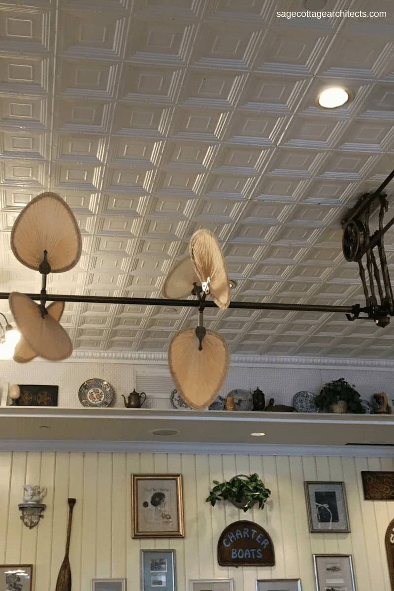 White tin ceiling, ceiling fan, and art work in Olivia's Cafe at Disney's Old Key West Resort.