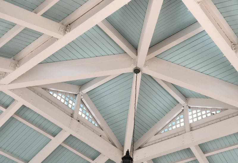 Exposed white rafters and blue wood slat roof of main entrance to Disney's Old Key West Resort.