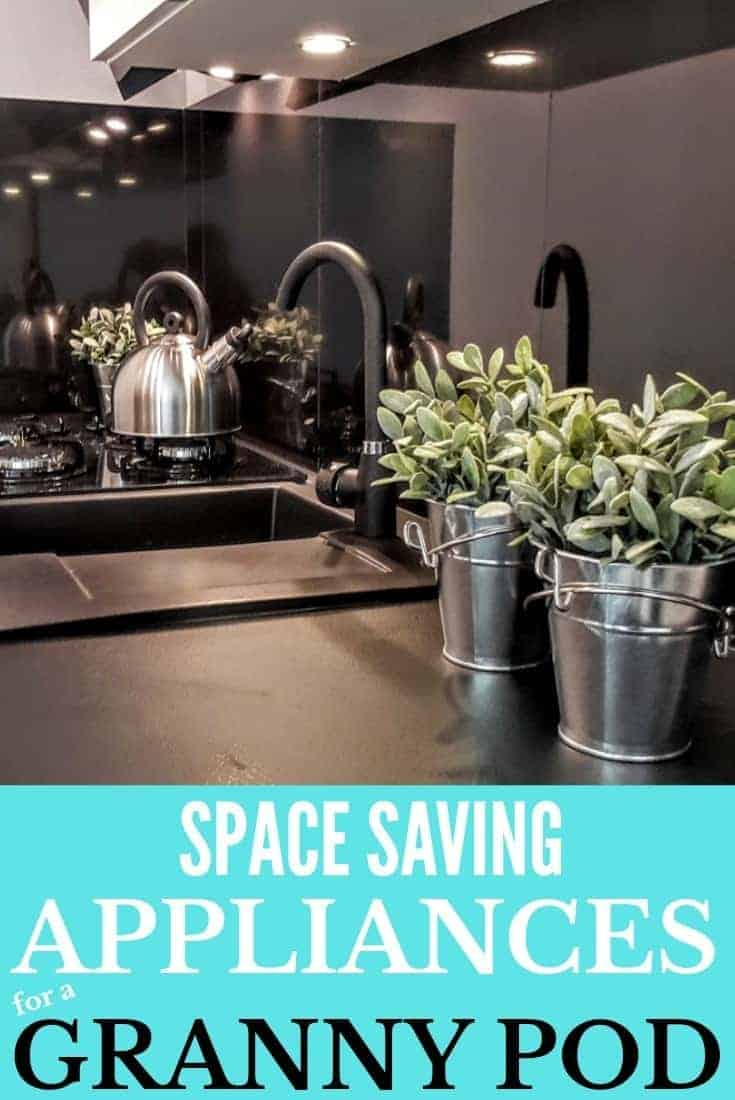 Compact black kitchen with sage plants growing in galvanized buckets.
