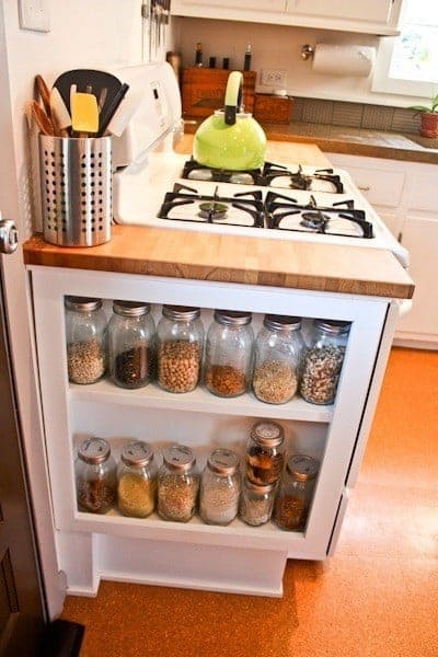 Display cabinet next to kitchen stove with mason jars are great storage ideas
