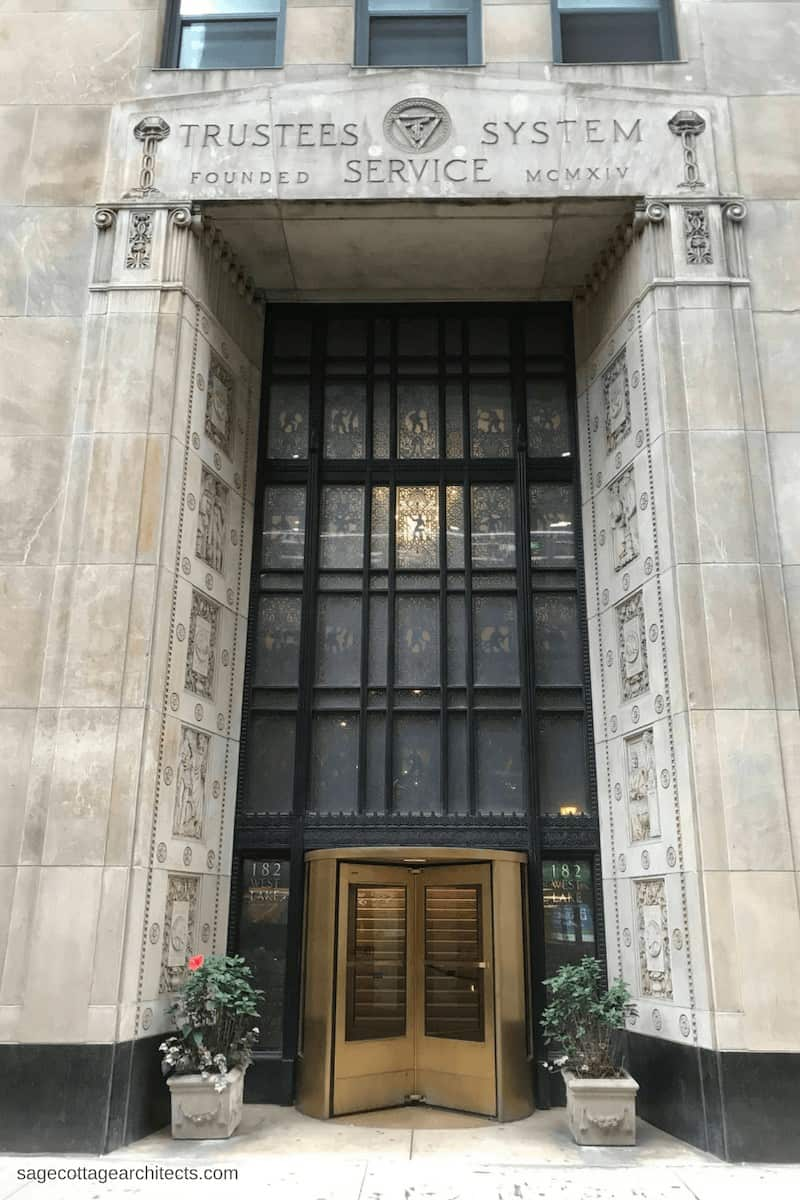 Art Deco Architecture: building entrance with black metal decorative panels and bronze revolving door.
