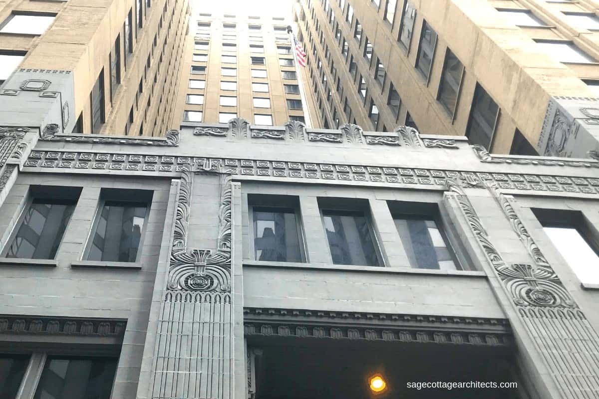 Looking up at an Art Deco skyscraper with grey base and tan upper floors