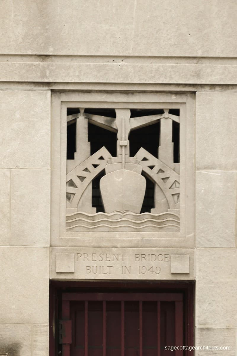 Art Deco styled carved limestone panel of a ship going under two lifted bridges