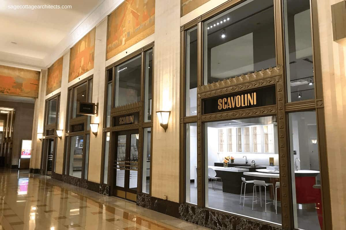 Art Deco lobby with terrazzo floors, decorative window frames and large murals.