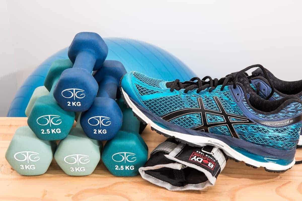 Photo of blue tennis shoe, dumbbells and blue workout ball that will be part of your best home gym.