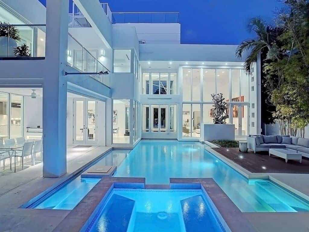 Photo of a modern style beach vacation home with a large pool at night.