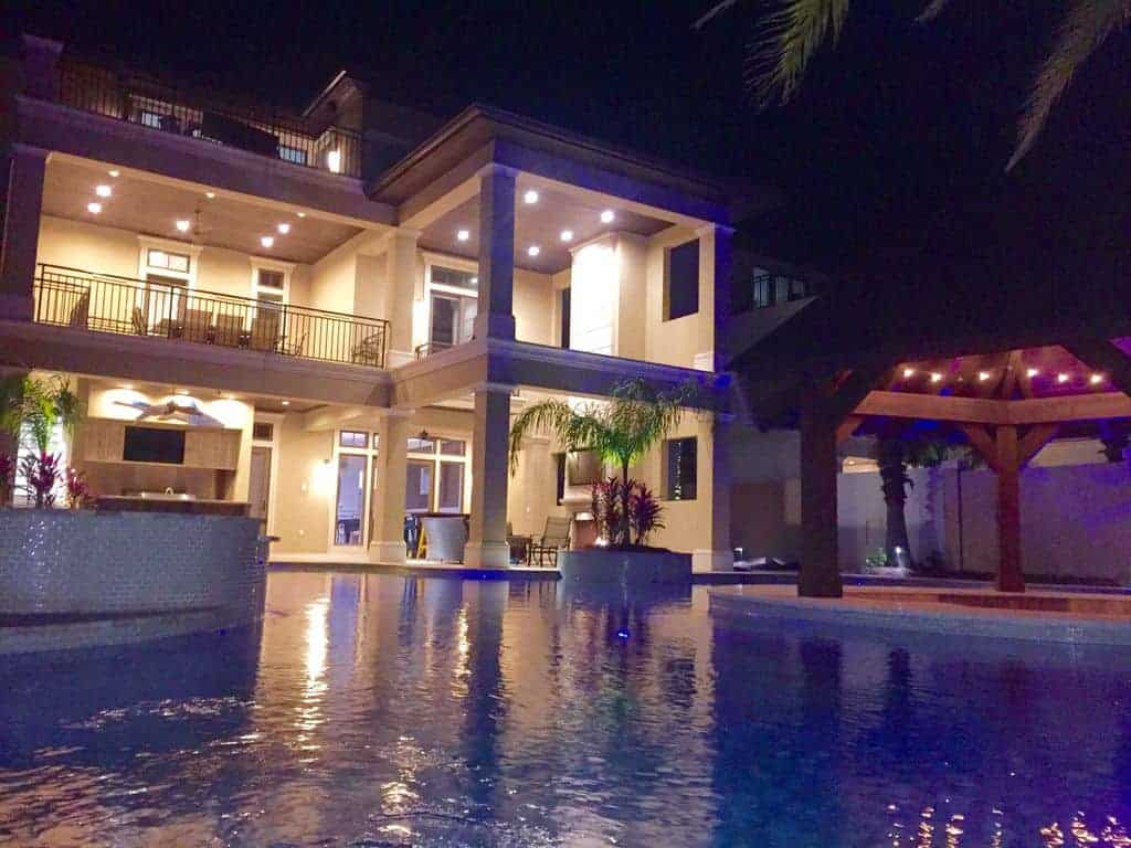 Photo of a large beach vacation home with a pool at night.