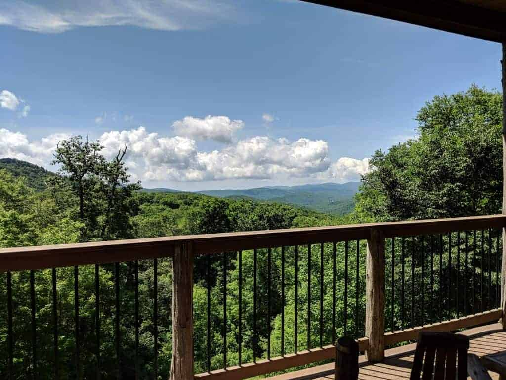 Picture of a ski vacation home rental in the summertime, looking over a porch railing at the Smoky Mountains.