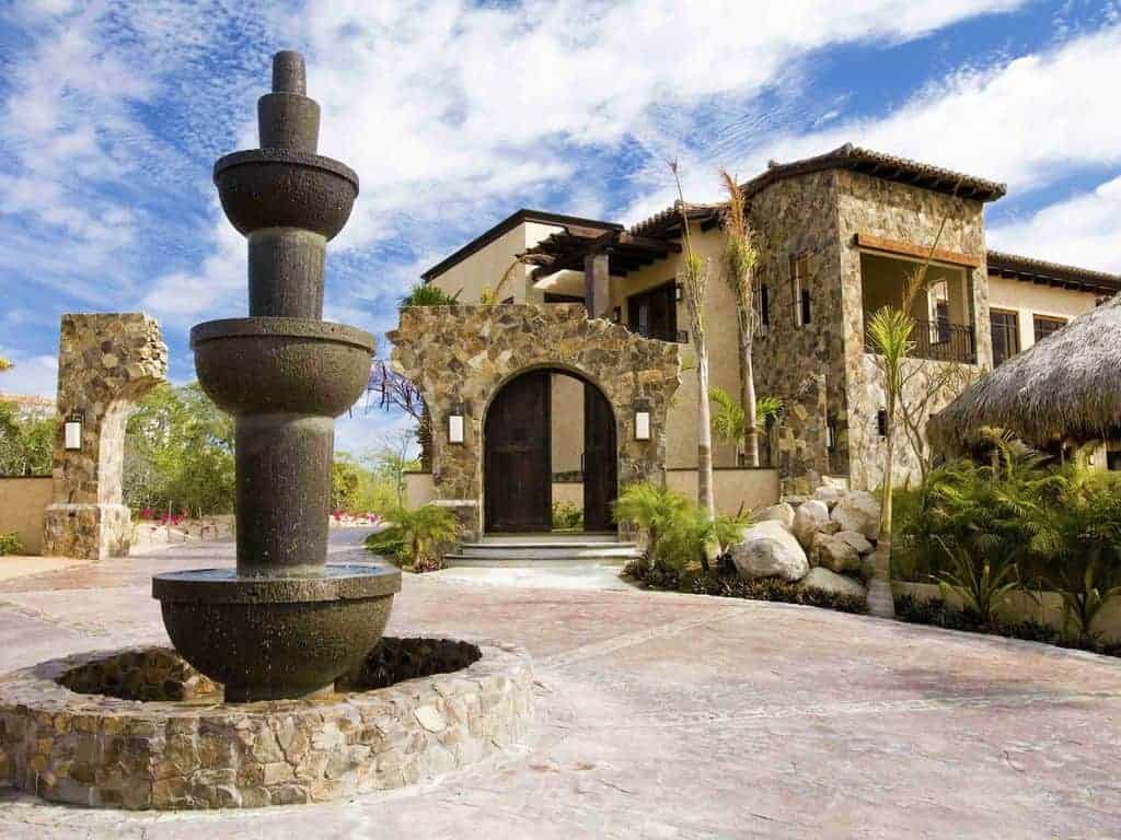 Photo of the entrance to a beach vacation rental home with rustic stone walls and a fountain.