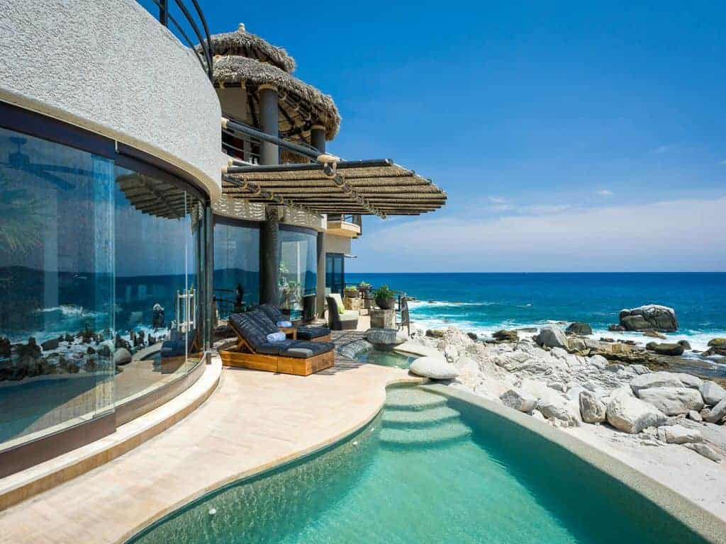 Photo of a glass and stucco beach home with pool.
