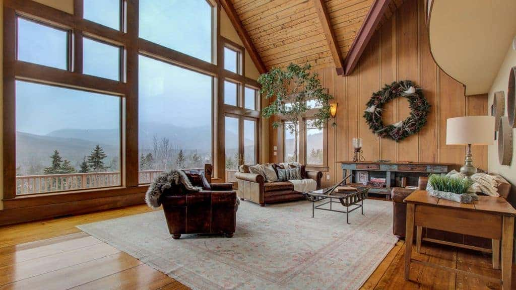 Interior photo of a ski vacation rental home with vaulted ceiling and window wall.