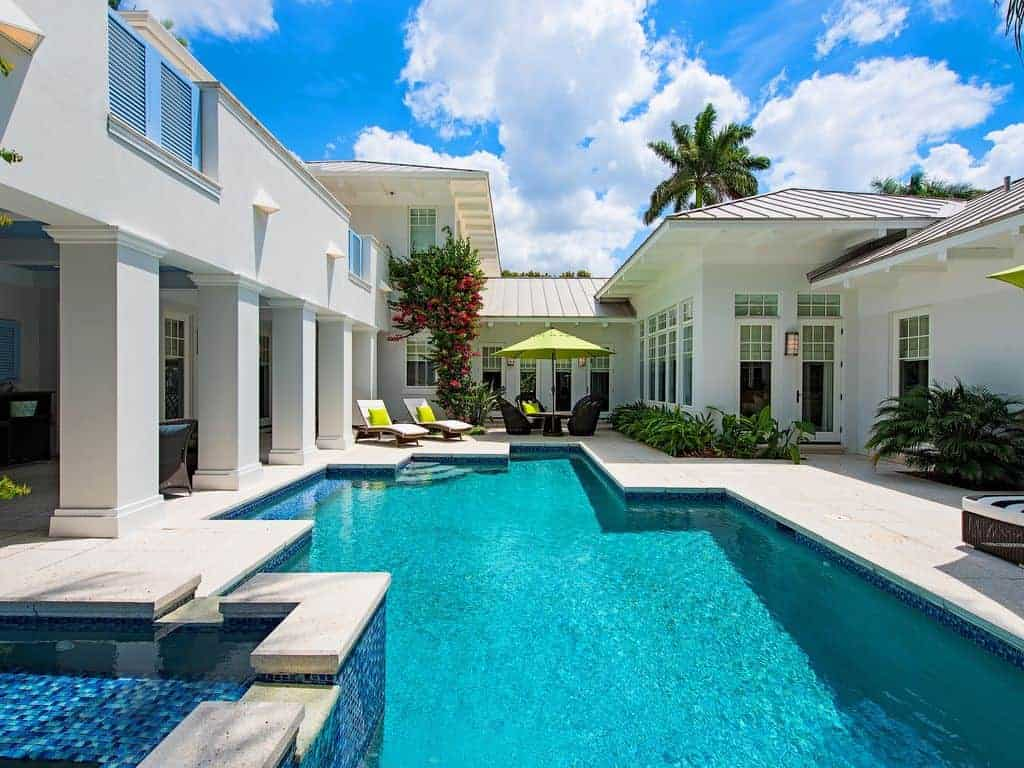 Photo of a white stucco home with a bright blue pool that is perfect for a beach vacation.