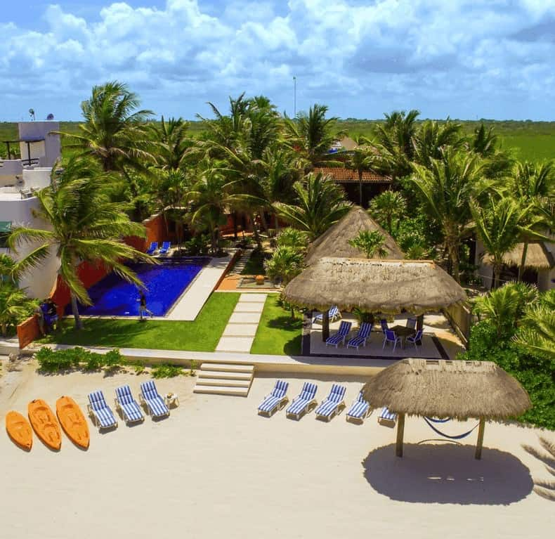 Photo of the ideal beach vacation home. Kayaks, lounge chairs, and thatched shade structures on the beach.