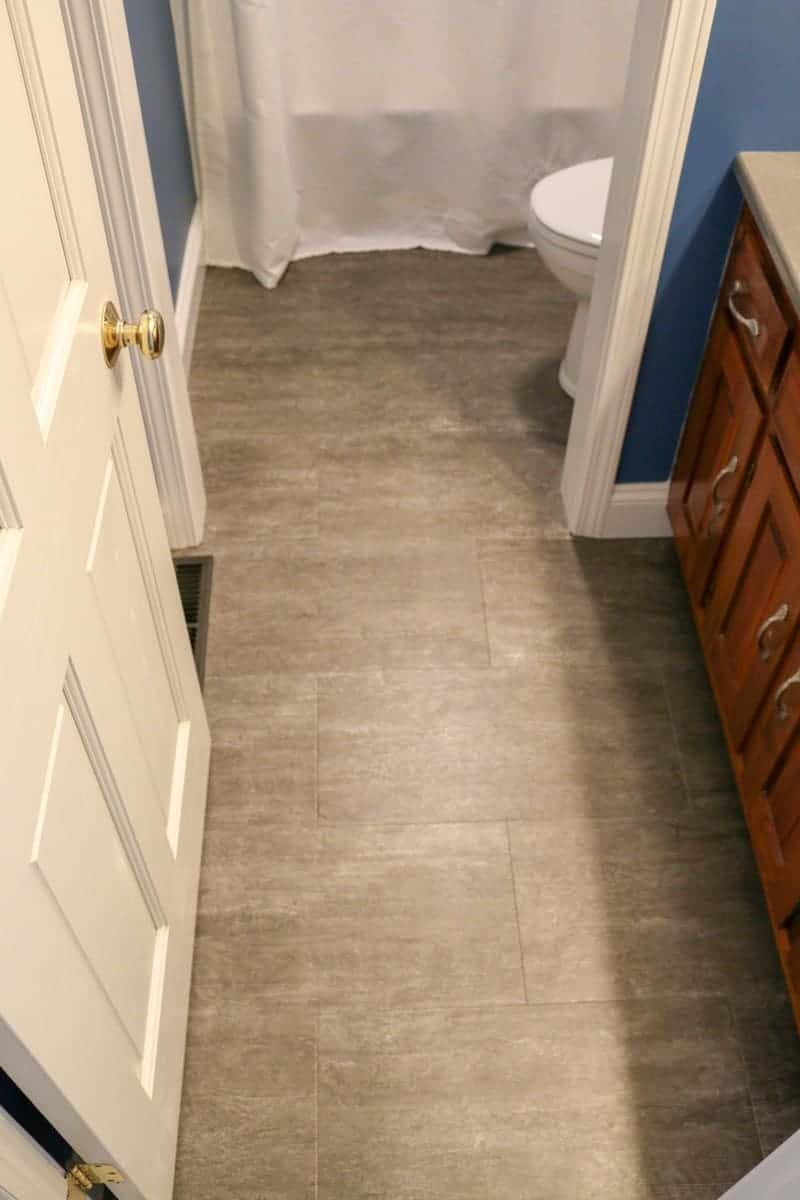 Photo of dark blue bathroom with grey luxury vinyl tile flooring