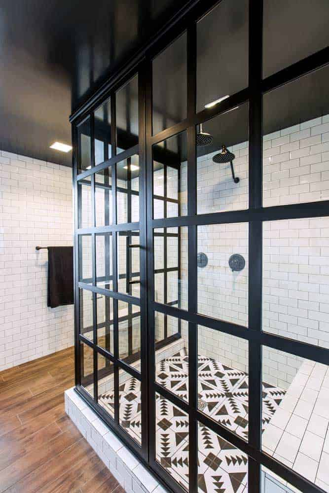 Photo of black framed glass shower enclosure with white subway tiles and black and white tile floor