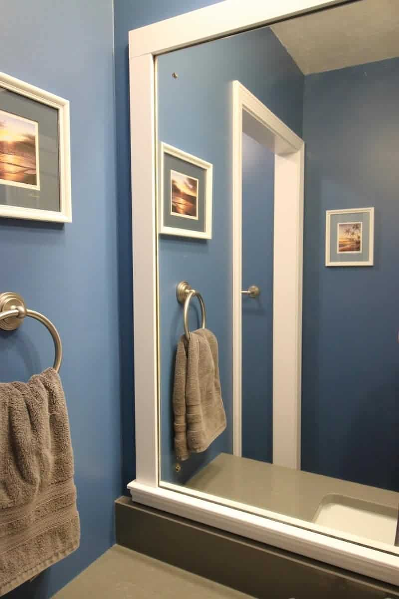 Photo of a dark blue bathroom with a white wood DIY bathroom mirror frame project