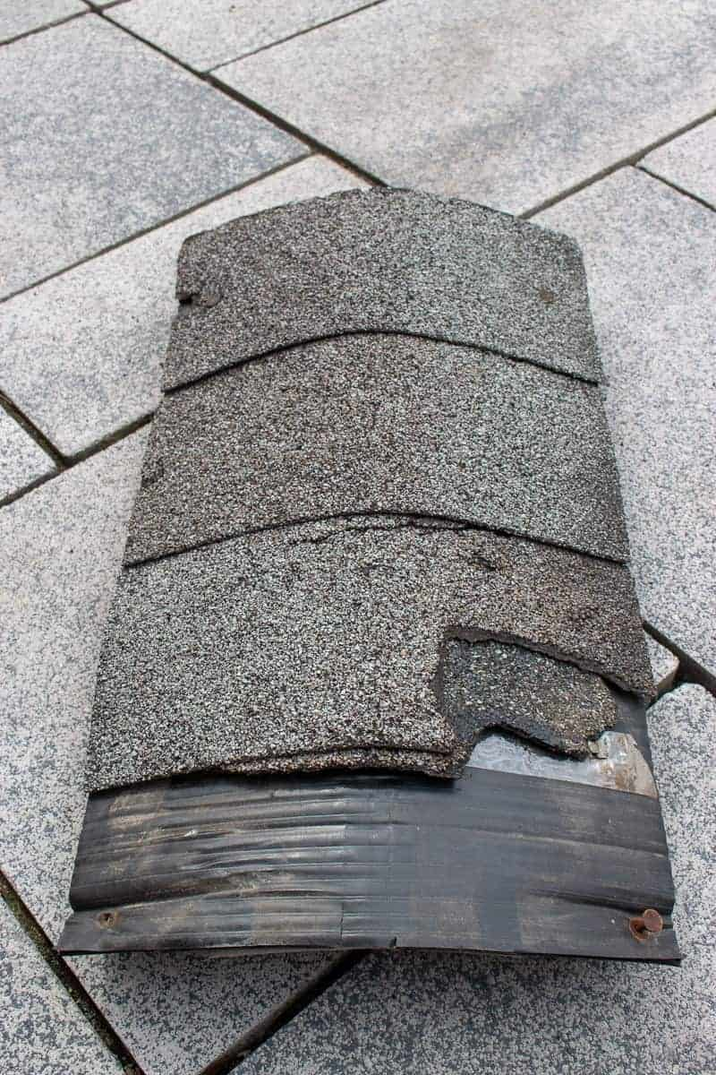 Photo of the old roof ridge vent with dark grey asphalt shingles