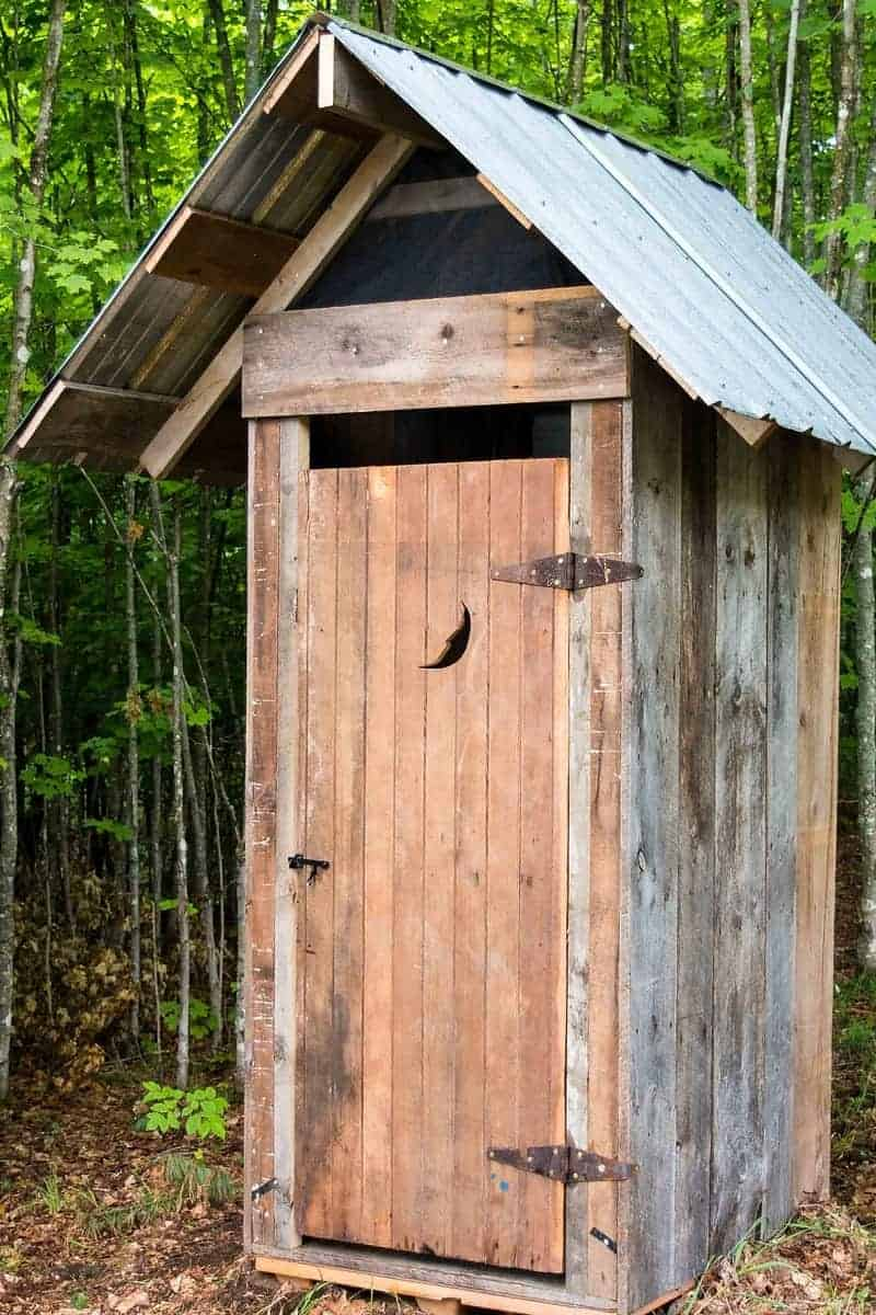 Photo of a rustic outhouse that is a form of septic systems.