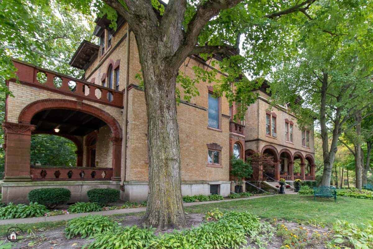 Photo of large brick mansion in a neighborhood of old houses.