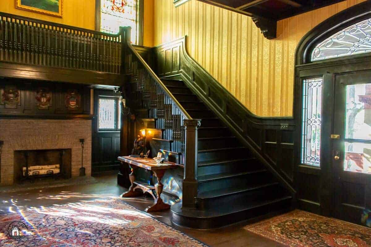Photo of black stained stairway and foyer of the Vrooman Mansion.