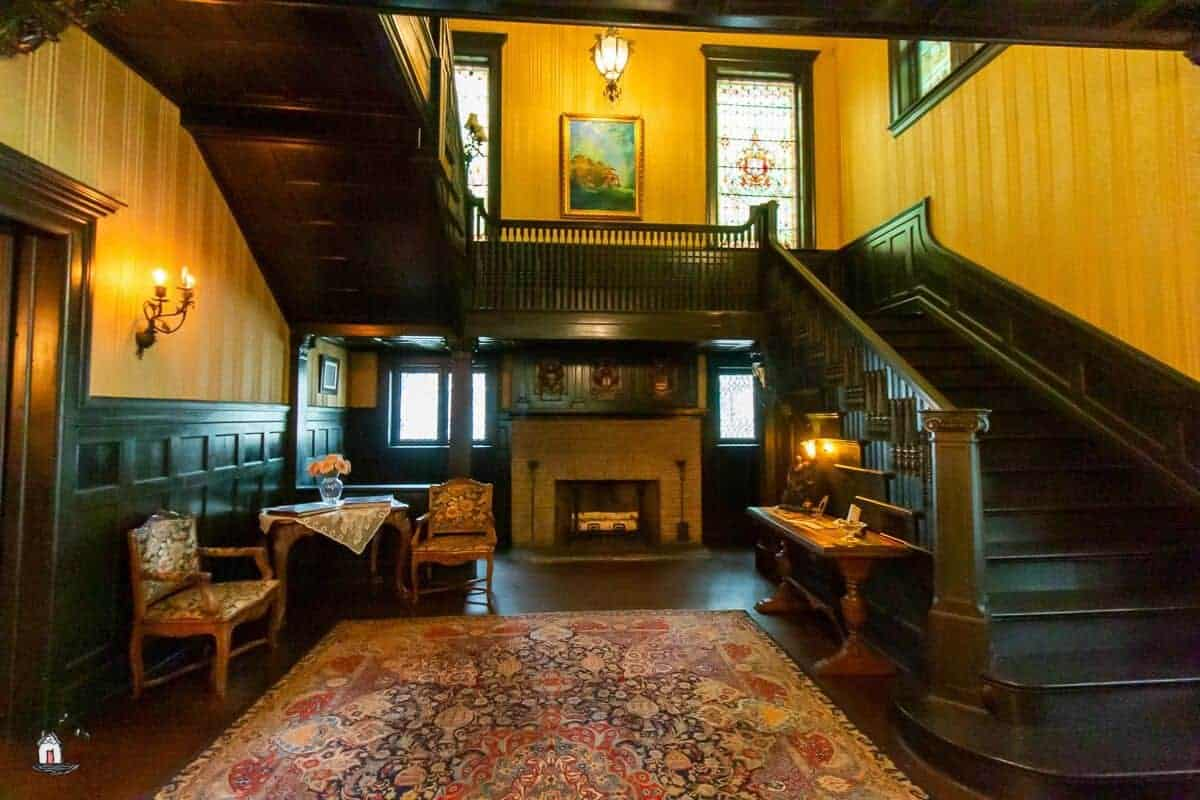 Photo of the interior of the Vrooman Mansion with dark stairs, fireplace, and large stained glass windows.