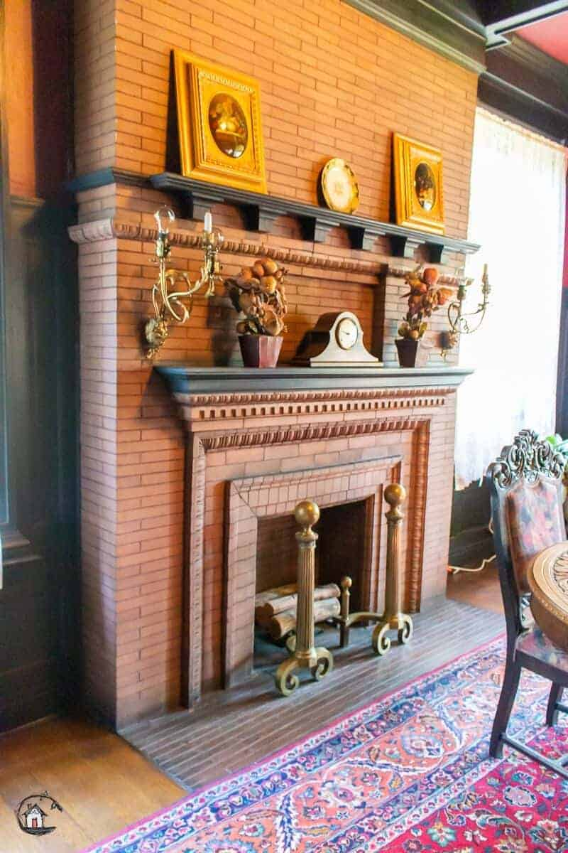 Photo of red brick fireplace in an old house. New houses can learn a lot from old homes.