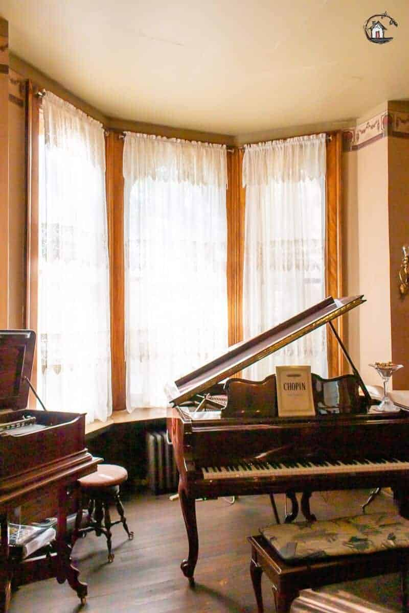 Photo of the Music Room with large windows and grand piano in the Vrooman Mansion.