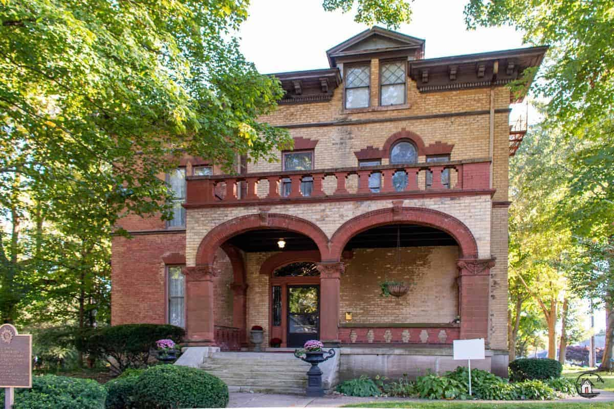 Photo of the front elevation of the Vrooman Mansion, with red brick archways and yellow brick walls.