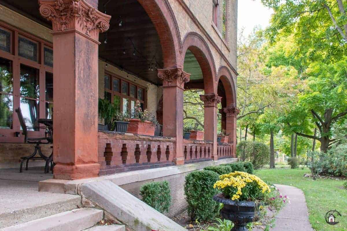 Photo of red brick arches, with ornate column capitals, on the side porch of the Vrooman Mansion.