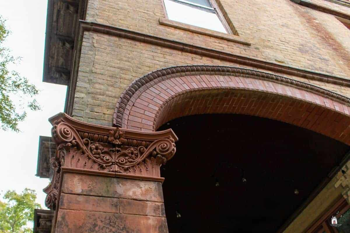 Photo of decorative brick column capital and arched opening on the Vrooman Mansion.