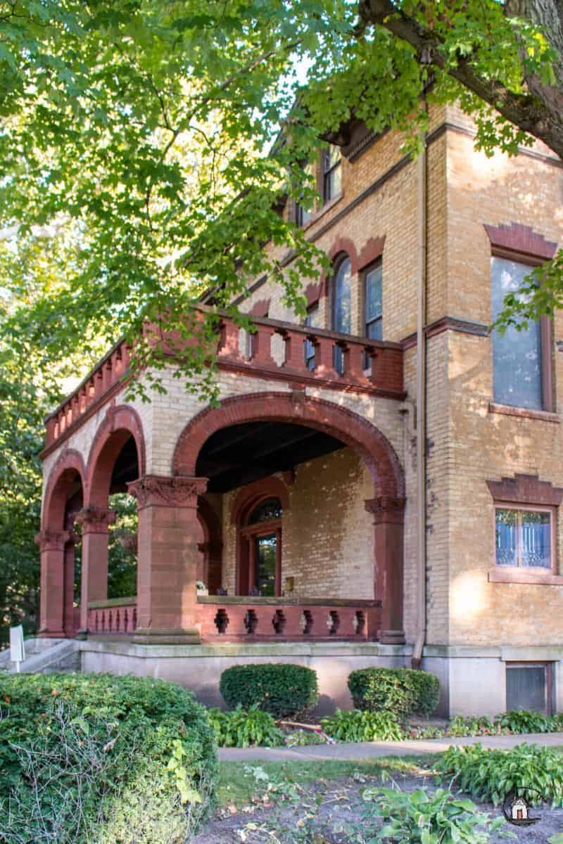 Photo of the entry porch of the Vrooman Mansion with red brick arched openings and railings.