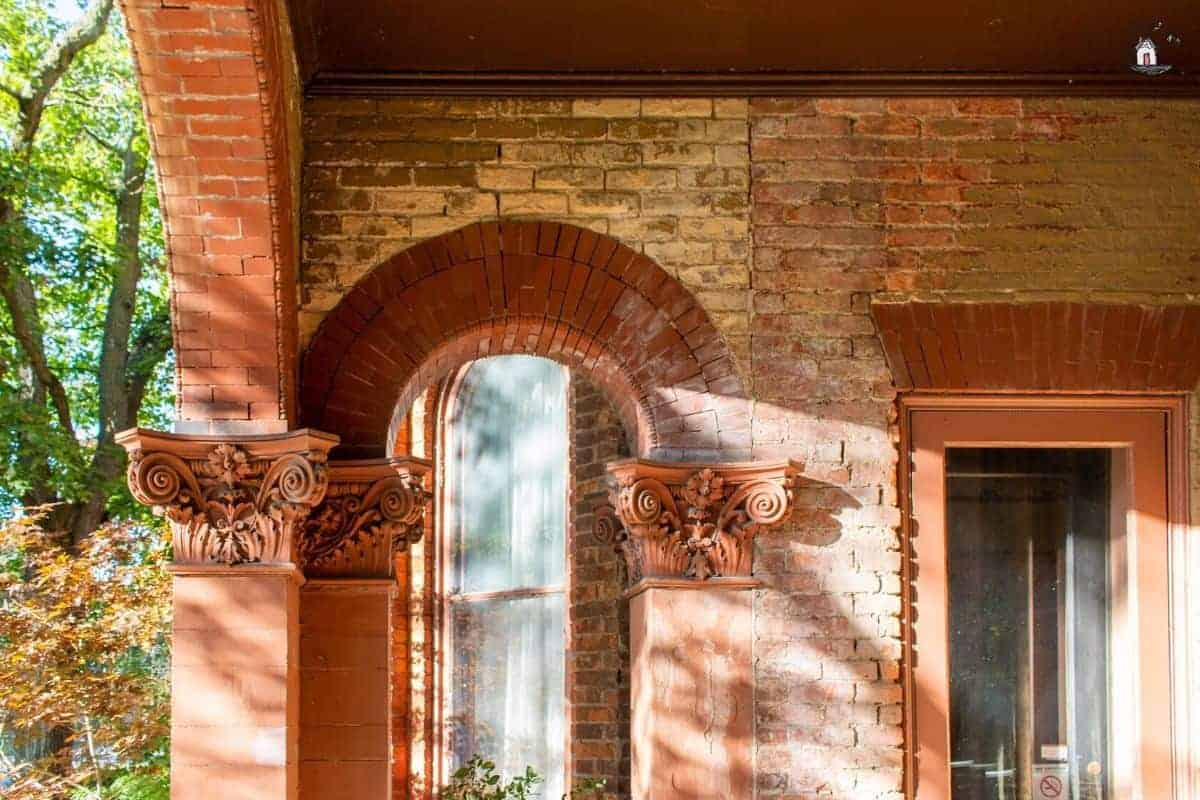 Photo of red brick arch with ornate column capitals at the Vrooman Mansion.