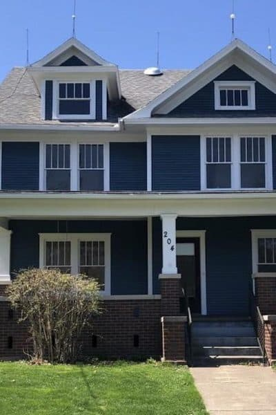 Photo of dark blue American Foursquare house with white trim