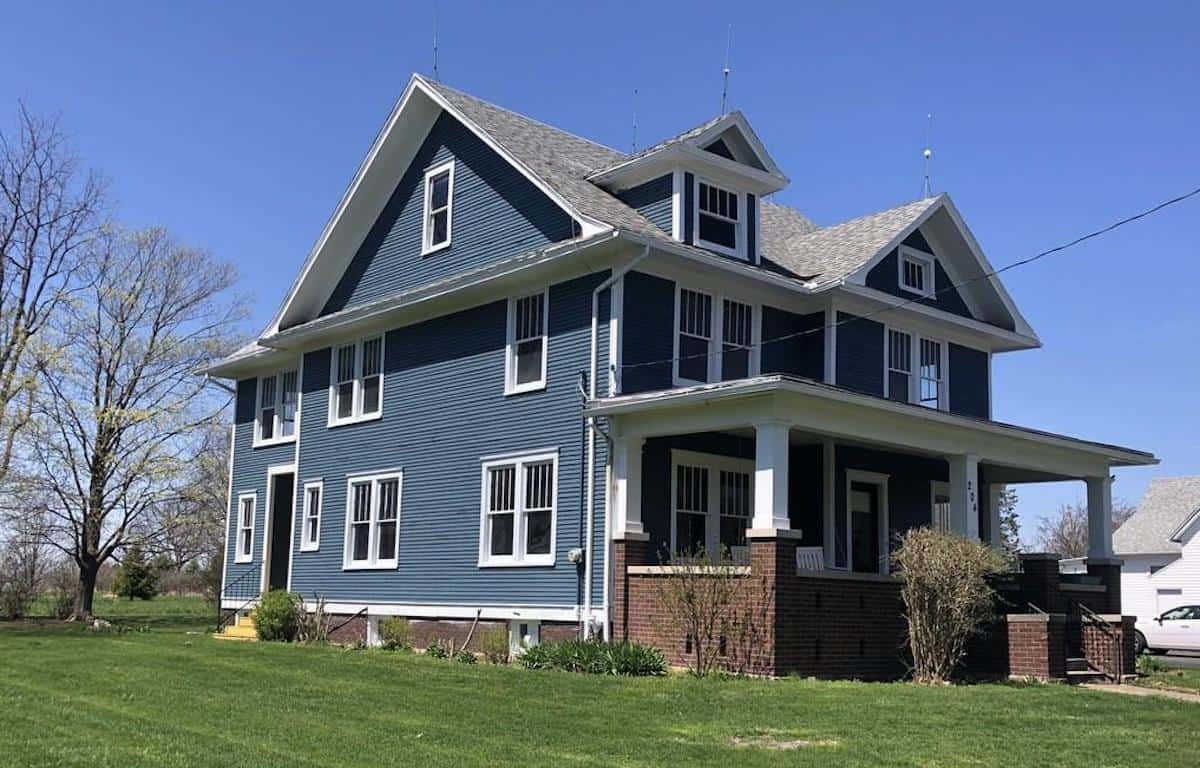Photo of dark blue American Foursquare house with white trim.