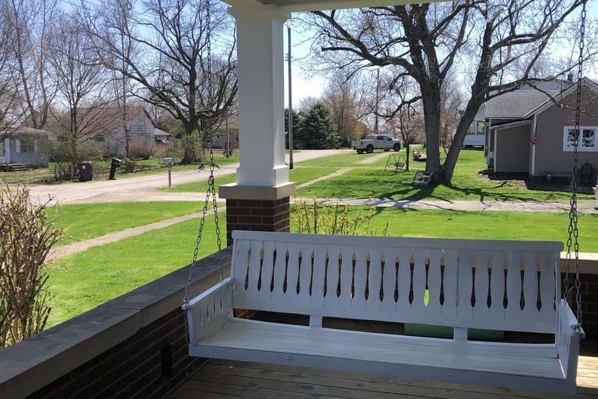 Photo of white porch swing on an American Foursquare style house.
