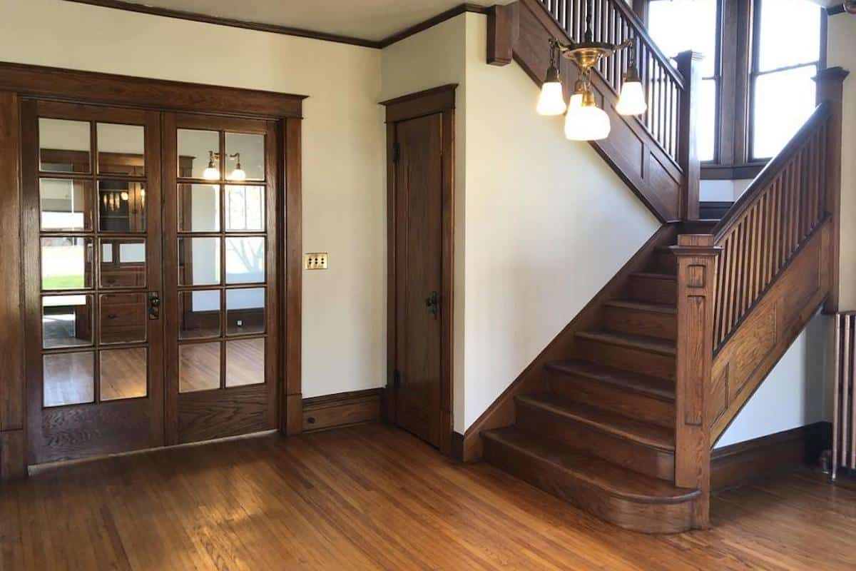 Photo of an American Foursquare home interior with oak stairs and French doors.