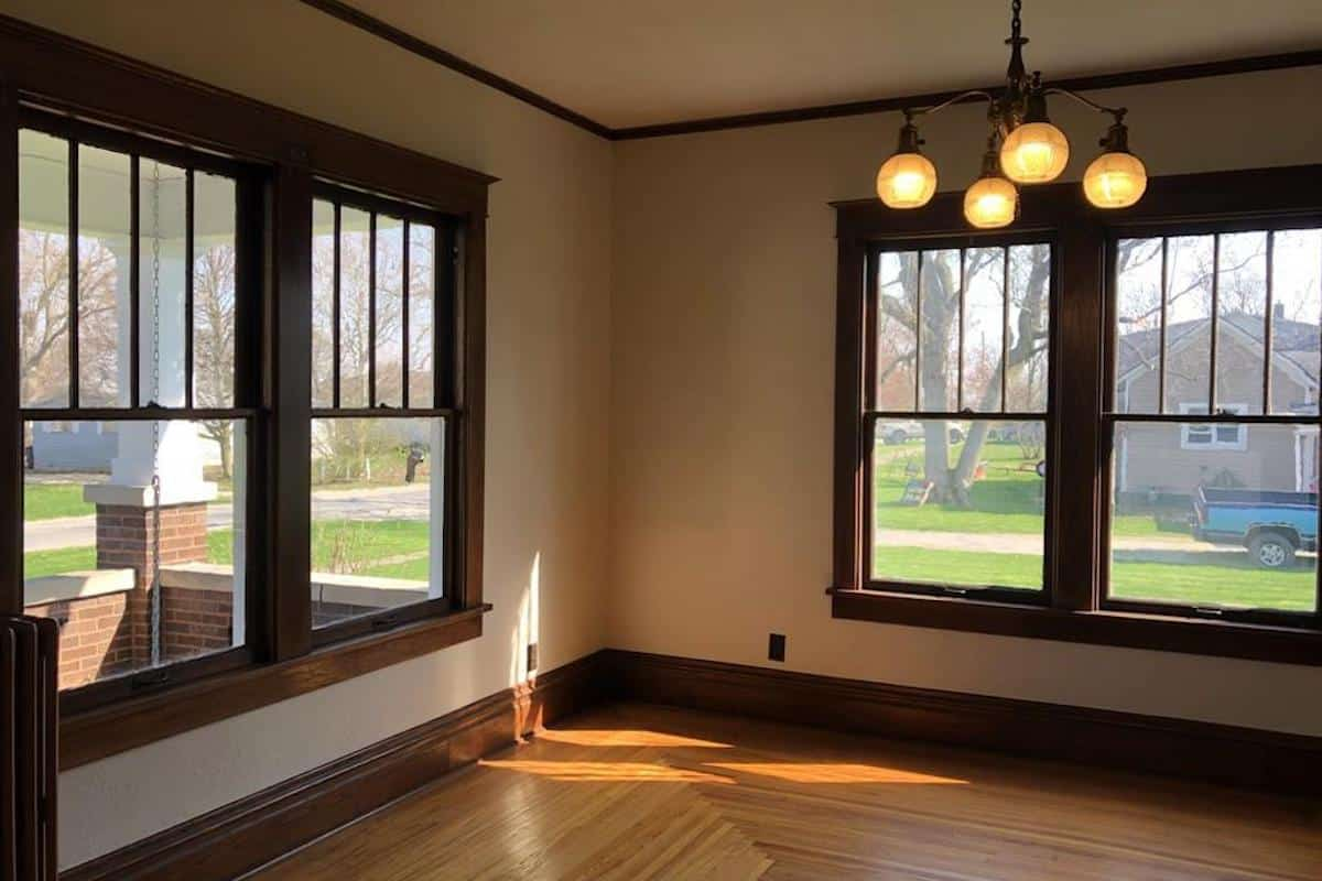 Photo of interior of an American Foursquare style home with large windows on two walls.